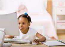 Muchacha que hace la preparación en el ordenador en dormitorio Fotos de archivo