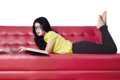 Muchacha que hace la preparación en el sofá Imagenes de archivo