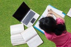 Muchacha que hace la preparación en la hierba en el parque Foto de archivo libre de regalías