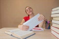 Muchacha que hace la preparación en la tabla en casa Estudiante de la chica joven con la pila de libros y de notas que estudia de Fotografía de archivo libre de regalías