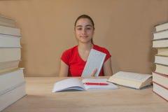 Muchacha que hace la preparación en la tabla en casa Estudiante de la chica joven con la pila de libros y de notas que estudia de Imagenes de archivo
