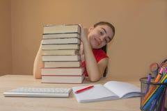 Muchacha que hace la preparación en la tabla en casa Estudiante de la chica joven con la pila de libros y de notas que estudia de Fotos de archivo libres de regalías