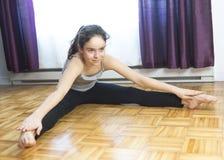 Muchacha que hace la yoga que se sienta en casa Foto de archivo libre de regalías