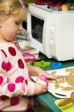 Muchacha que hace las galletas de la Navidad Imagenes de archivo