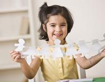 Muchacha que hace las muñecas de papel Foto de archivo