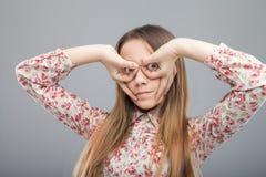 Muchacha que hace los vidrios con los fingeres Fotografía de archivo