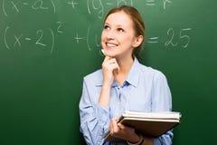 Muchacha que hace matemáticas en la pizarra Foto de archivo