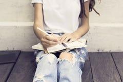 Muchacha que hace notas en el diario y que se sienta en un piso de madera Imagenes de archivo