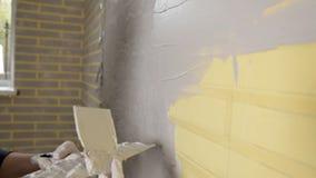 Muchacha que hace reparaciones en el apartamento Una mujer conduce una espátula en un muro de cemento Reparación del plano Masill metrajes