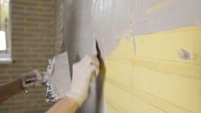 Muchacha que hace reparaciones en el apartamento Una mujer conduce una esp?tula en un muro de cemento Reparaci?n del plano Masill almacen de video
