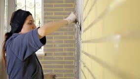 Muchacha que hace reparaciones en el apartamento Una mujer conduce una esp?tula en un muro de cemento Reparaci?n del plano Masill almacen de metraje de vídeo
