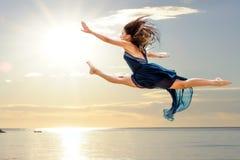 Muchacha que hace salto artístico en la puesta del sol Imagen de archivo libre de regalías