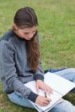 Muchacha que hace su preparación mientras que se sienta en la hierba Imagen de archivo