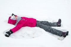 Muchacha que hace un ángel de la nieve Imágenes de archivo libres de regalías