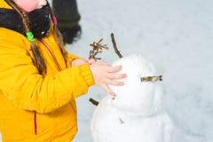 Muchacha que hace un muñeco de nieve las manos eran frías sin los guantes imágenes de archivo libres de regalías