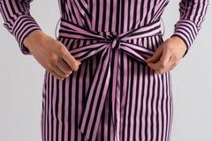 Muchacha que hace un presente de sí misma Atar un arco en vestido fotografía de archivo libre de regalías