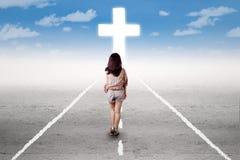 Muchacha que hace un viaje santo a la cruz Fotografía de archivo