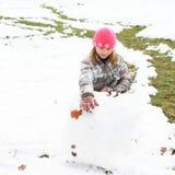 Muchacha que hace una bola grande de la nieve Imagen de archivo libre de regalías