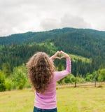 Muchacha que hace una corazón-forma con paisaje de la montaña en el fondo fotografía de archivo