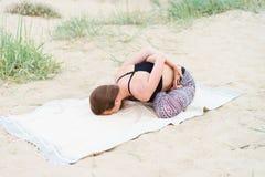 Muchacha que hace yoga al aire libre en la posición de Lotus respecto a la playa Imagen de archivo libre de regalías