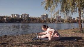 Muchacha que hace yoga en el parque en un fondo del río almacen de metraje de vídeo
