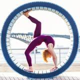 Muchacha que hace yoga en un anillo en la playa Fotografía de archivo libre de regalías