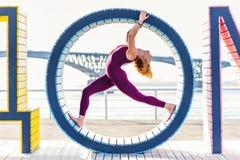 Muchacha que hace yoga en un anillo en la playa Foto de archivo libre de regalías