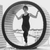 Muchacha que hace yoga en un anillo en la playa Imagenes de archivo