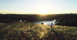 Muchacha que hace yoga en un prado hermoso en la puesta del sol Cámara lenta