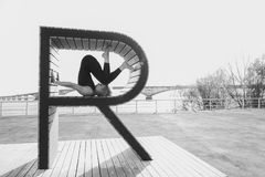 Muchacha que hace yoga en una letra en la playa Foto de archivo libre de regalías