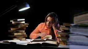 Muchacha que hojea con un libro y caer dormidos en la tabla Fondo negro almacen de metraje de vídeo