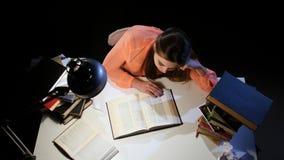 Muchacha que hojea con un libro y caer dormidos en la tabla Fondo negro Visión desde arriba metrajes