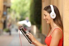 Muchacha que hojea una tableta y que escucha con los auriculares Foto de archivo libre de regalías