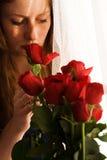 Muchacha que huele rosas rojas Foto de archivo libre de regalías