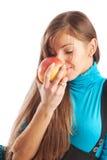 Muchacha que huele una manzana Foto de archivo