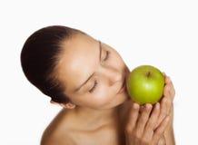 Muchacha que huele una manzana verde Foto de archivo libre de regalías