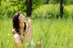 Muchacha que infla burbujas de jabón Foto de archivo