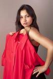 Muchacha que intenta encendido la camisa roja en departamento Fotografía de archivo libre de regalías
