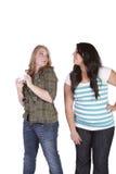 Muchacha que intenta mirar el mensaje del texto de su amigo Imagen de archivo libre de regalías