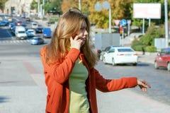 Muchacha que intenta parar el coche en el camino Imagen de archivo libre de regalías