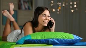 Muchacha que invita al teléfono en una cama en casa almacen de metraje de vídeo