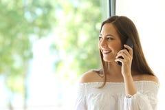 Muchacha que invita a la línea horizonte del teléfono en casa Foto de archivo
