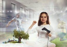 Muchacha que juega al juego video Técnicas mixtas Foto de archivo