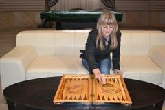 Muchacha que juega a backgammon Imagenes de archivo