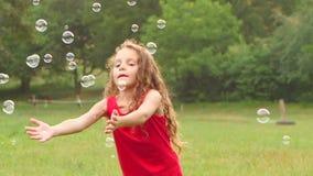Muchacha que juega burbujas de jabón de la captura en el jardín Cámara lenta Cierre para arriba almacen de video