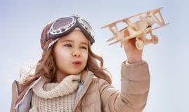 Muchacha que juega con el aeroplano del juguete Imagen de archivo
