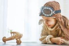 Muchacha que juega con el aeroplano del juguete foto de archivo