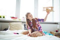 Muchacha que juega con el aeroplano en cama Imagen de archivo libre de regalías