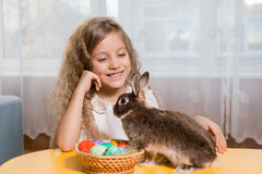 Muchacha que juega con el conejito de pascua Foto de archivo