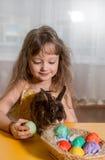 Muchacha que juega con el conejito de pascua Foto de archivo libre de regalías